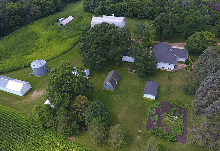 Aerial view of a Minnesota family farm with a house, out buildings, silo, and crop land | Farm Insurance
