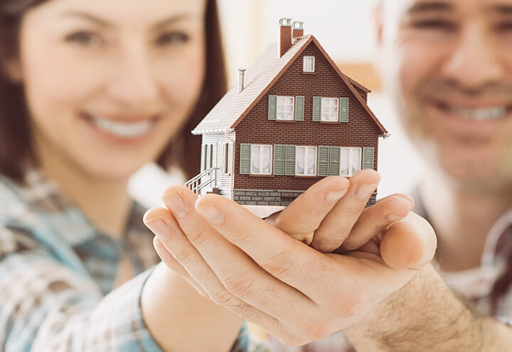 Young smiling couple holding up the model of a house | Homeowners Insurance