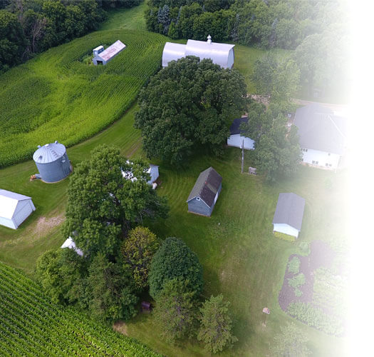 Aerial photo of a rural family farm in Minnesota with a house, barn, sheds, silo, garden, and crop fields | Farm Insurance